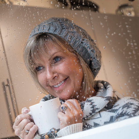 Woman in winter hat with warm cup of hot chocolate