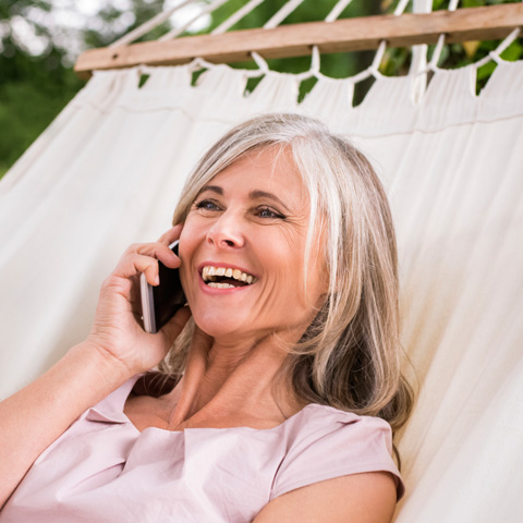 Older woman on her cell phone smiling in a hammock
