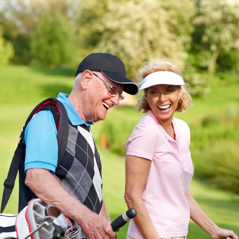 Older couple smiling on golf course